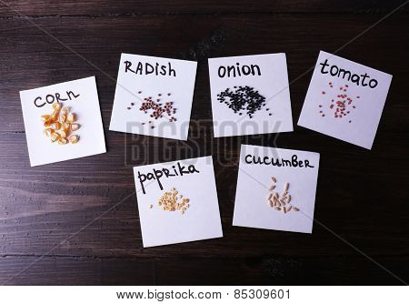 Different seeds on pieces of paper on wooden background