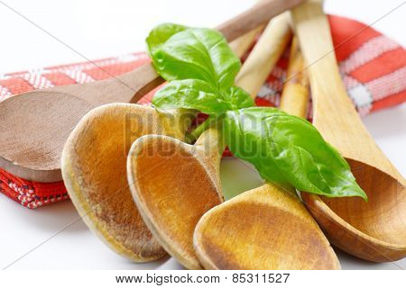 detail of old wooden spoons and fresh basil on checkered dishtowel