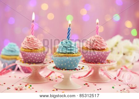 Delicious cupcakes on table on bright background