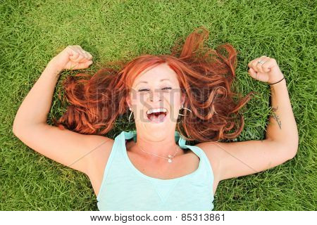 a pretty woman lying in green grass laughing and flexing her muscles