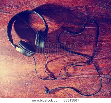 headphones and the cord in the shape of a heart symbolic of a love for music on an antique wooden texture background toned with a retro vintage instagram filter effect app or action