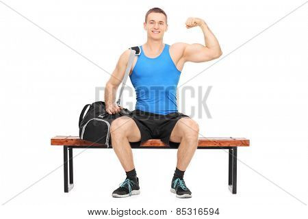 Muscular athlete showing his bicep seated on a bench isolated on white background