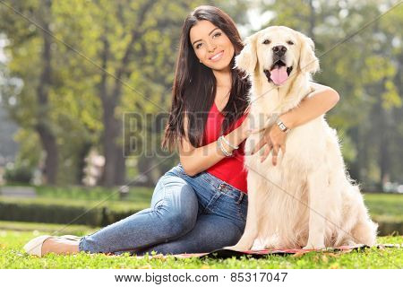 Young girl posing with her dog in a park