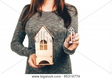 Woman holding house and keys in her hands