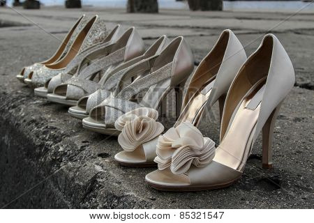 High heel wedding shoes lined up on stone pier
