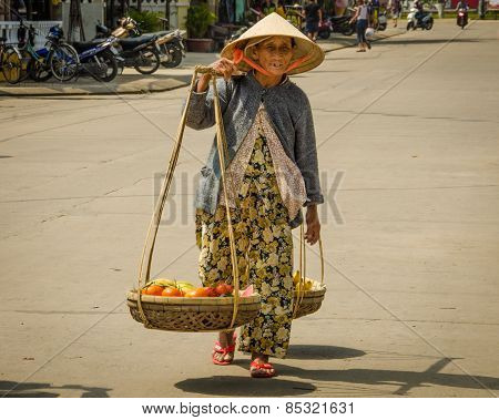 An old Vietnamese woman carries a heavy load of fruit in baskets for sale.