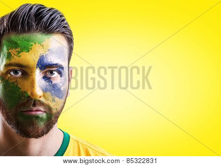 Man with his face painted with the Brazilian Flag on yellow background