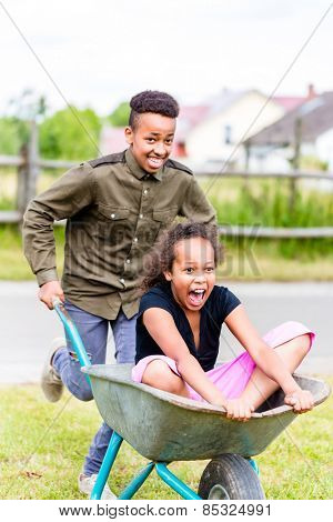 Siblings playing together in garden pushing each other in wheelbarrow