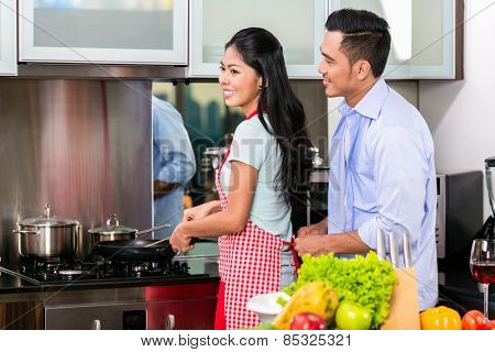 Couple in domestic Kitchen cooking food