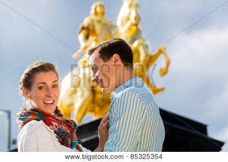 Tourist couple in Dresden in front of Goldener Reiter statue