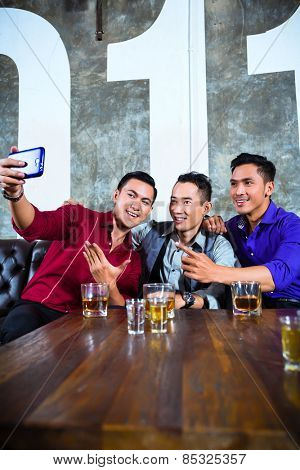 Asian party people group of young friends taking pictures or selfies with their mobile or cell phone in fancy night club