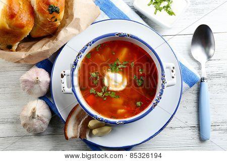 Ukrainian beetroot soup - borscht, on blue napkin, on wooden background
