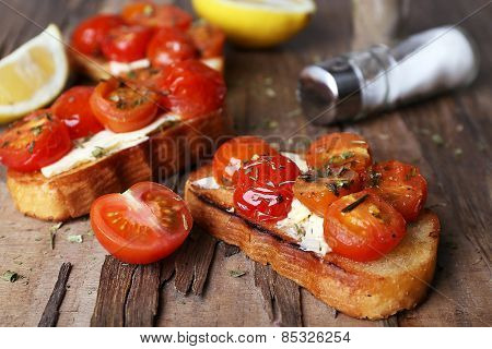 Slices of white toasted bread with canned tomatoes and lime on wooden table, closeup