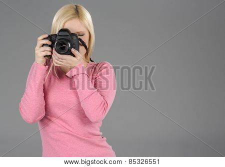 Blonde model holding a camera in a studio environment