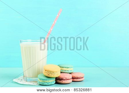 Assortment of gentle colorful macaroons and glass with milk on color wooden background