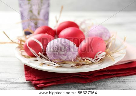 Easter composition with colorful eggs on plate on wooden table background