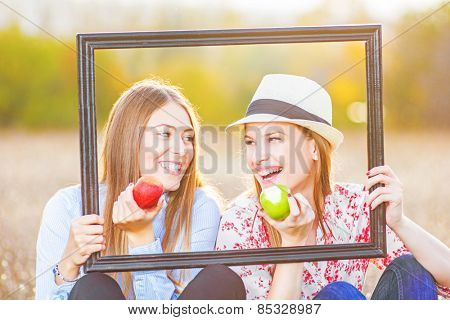 Two friends holding picture frame outside