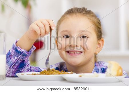 Child at table with fork