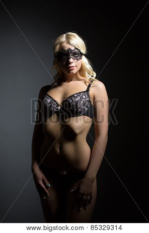 Charming slim model in lingerie and mask