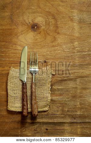 cutlery (knife and fork) on wooden background