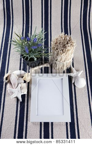 Beautiful vintage collage with white photo frame on an old rug, with sea shells and starfish.