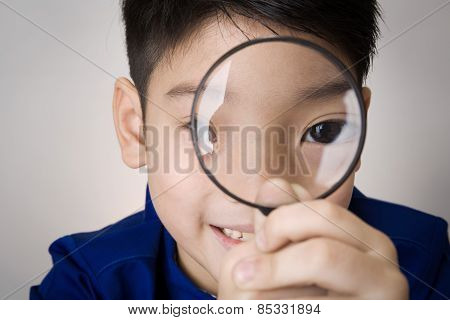 Portrait Of A Young Asian Child Looking Through A Magnifying Glass