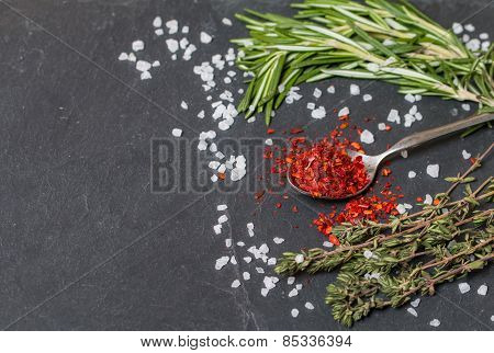 Spoons With Hot Pepper And Herbs On  Black