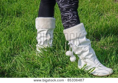 Legs In Black Stockings And White Boots On Green Grass