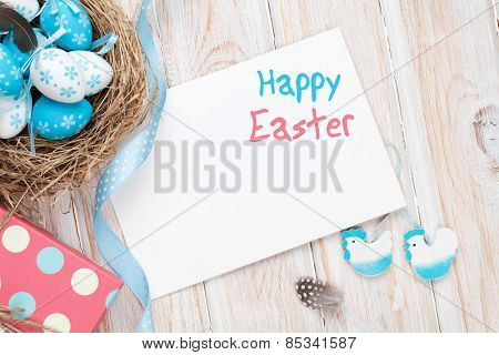 Easter greeting card with blue and white eggs and gift box over white wood. Top view with copy space