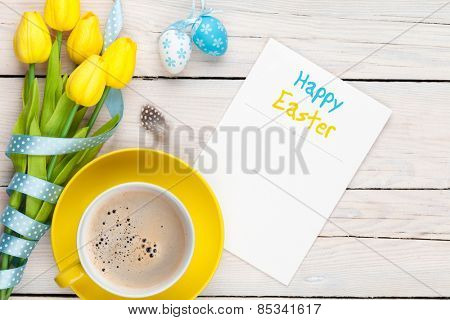 Easter greeting card with blue and white eggs, yellow tulips and coffee cup over white wood. Top view with copy space