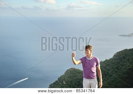 Young Man Taking Selfie On Top Of A Mountain Over Sea