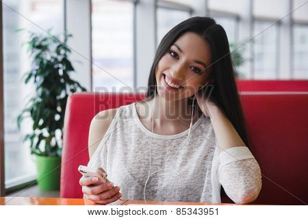 Beautiful Girl Listening To Music On The Phone With Headphones