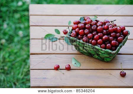 Juicy Ripe Cherries In A Basket On Wooden Table Outdoor