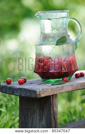 Jug Of Cold Fresh Water With Cherries On Wooden Table In The Garden