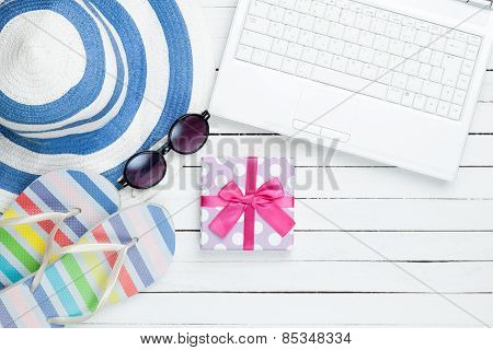 White Computer And Flip Flops Shoes With Clothes And Gift Box