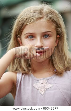 Mustache.Portrait of teenage girl with painted mustache on finger