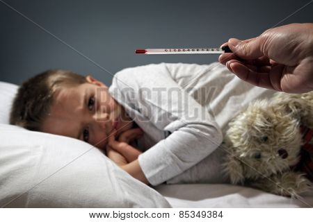 Poorly boy in bed with a thermometer reading high temperature