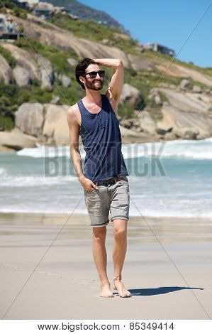 Happy Young Man On Vacation Walking Barefoot On Beach