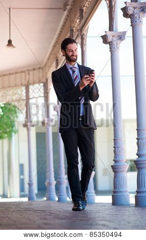 Happy Businessman Sending Text Message On Mobile Phone