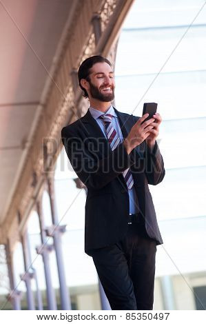 Smiling Businessman Sending Text Message On Cell Phone