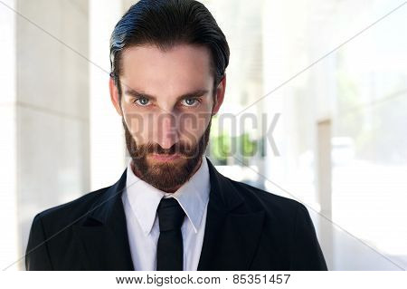 Confident Young Businessman With Beard In Black Suit And Tie
