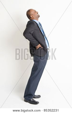 Full body Indian businessman backache, holding his spine with painful face expression, standing on plain background.
