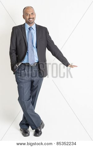 Full body Asian Indian businessman putting hand on invisible banner over plain background