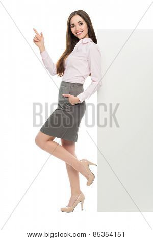 Beautiful woman leaning against big white poster
