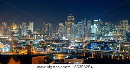 San Francisco city skyline with urban architectures at night with highway bridge panorama.