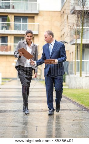Two Business People Walking And Discussing