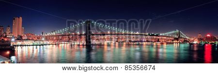 Brooklyn Bridge panorama over East River at night in New York City Manhattan with lights and reflections.