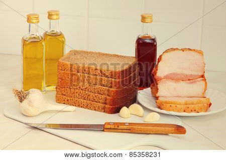 Sliced Bread,bacon And Olive Oil On Kitchen Table.