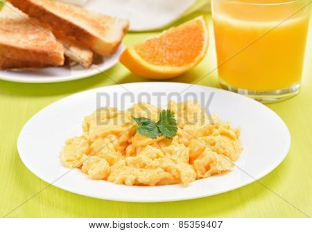 Scrambled Eggs On White Plate, Toast And Orange Juice