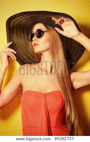 Portrait of a stunning fashionable lady over bright yellow background. Beauty, fashion concept. Optics.